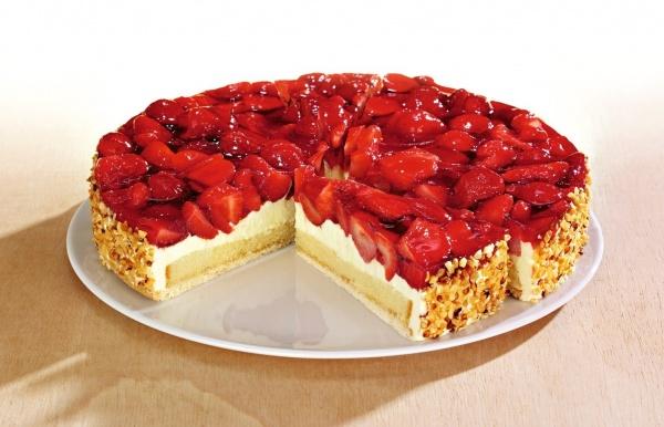 Una base de masa quebrada cubierta por un bizcocho con cremoso de nata cubierta por deliciosas medias fresas. Lleva un recubrimiento de corcante de avellana.