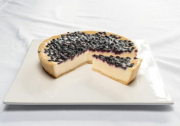 Deliciosa masa de mezcla de quesos y nata sobre una masa de grumos de mantequilla, cubierta con arándanos enteros.