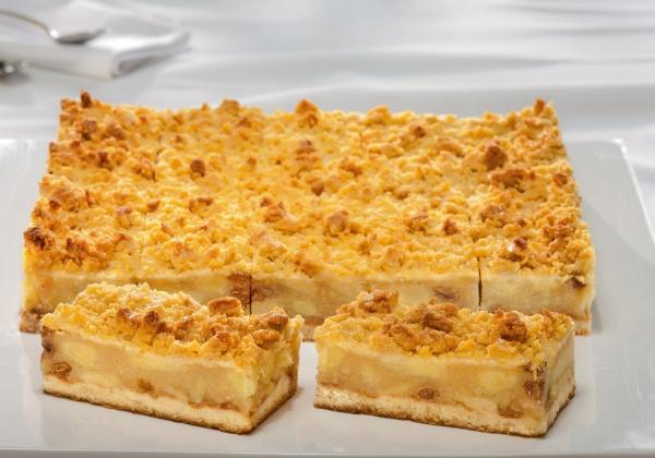 Una tradicional masa hecha en base a requesón cubierta con trozos de manzana, pasas y grumos de mantequilla.