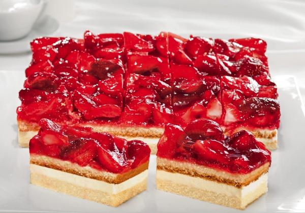 Plancha con crema de suero de leche fresca entre dos capas de esponja ligera, con mitades de fresa y jalea afrutada.