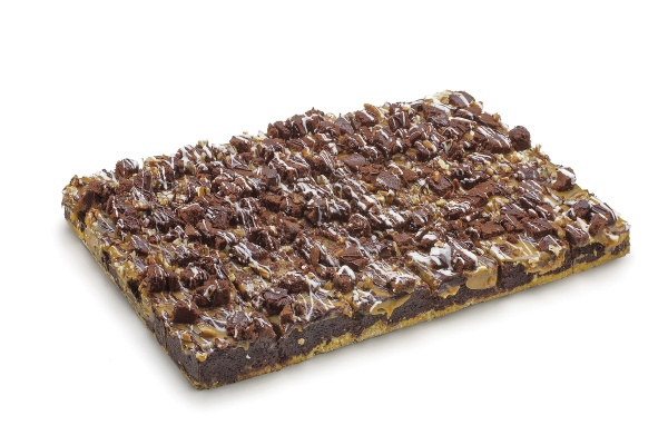 Una base de crumble, brownie en el medio y una fina capa de caramelo, daditos de bizcocho de chocolate, nueces pecan y una decoración de cobertura de choclate blanco y negro