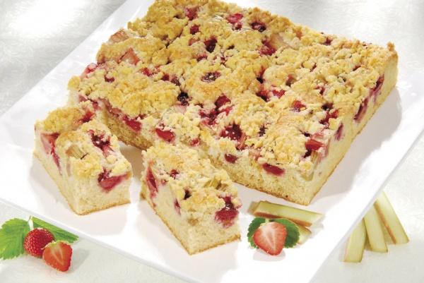 Trocitos de ruibarbo y fresa sobre una ligera y esponjosa masa, cubierta de grumos de mantequilla.