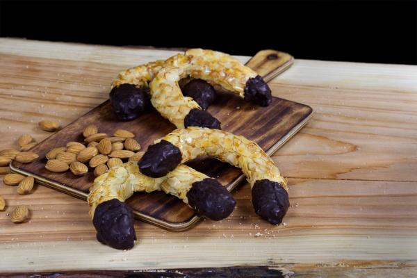 Crujiente mazapán espolvoreado con almendra laminada y puntas bañadas de chocolate. En forma de herradura de la suerte. ¡Suerte para quien la coma!